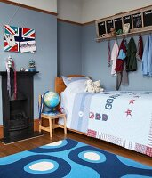 Teenager's bedroom with blue-painted walls, clothes rack with chalkboards and magnetic pinboard with Union Flag pattern