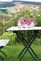 Pink hydrangeas in enamel bowl on folding garden table in front of bed of ox-eye daisies