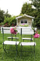 Folding chairs decorated with hydrangea flowers on lawn in front of romantic, pastel yellow summer house