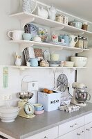 Nostalgic appliances on kitchen counter below vintage and retro crockery on bracket shelves