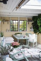 Wooden lounger, table and chairs in pastel-yellow, romantic loggia with lattice windows and wooden wall