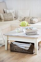 White, vintage coffee table and old, wooden crate in front of corner bench with various scatter cushions