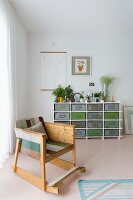Rocking chair made from multicoloured wooden boards and sideboard holding vintage metal crates against wall in modern interior