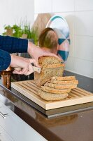 Hands slicing bread with knife in kitchen