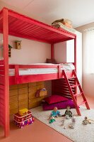 Wooden loft bed with ladder stained light red and toys on rug in child's bedroom