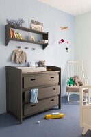 Changing table painted grey brown below matching shelves on wall painted pale blue and white rocking chair in corner to one side