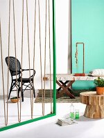 Green wooden frame strung with rope as partition, bench with fabric seat, lamp made from copper piping and rope