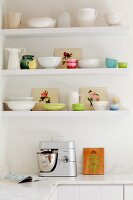 Pastel and white nostalgic crockery on floating shelves on white kitchen wall above mixer on marble worksurface