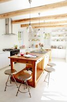 Vintage metal stools around free-standing, solid-wood island counter in bright, sunny kitchen with wood-beamed ceiling