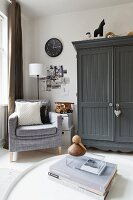 Corner of comfortable living room with pale grey armchair, collage on wall and farmhouse cupboard painted dark grey
