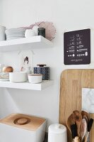 Stacked crockery on white floating shelves above bread bin and kitchen utensils