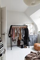 Black clothes rack next to vintage cabinet in corner of bedroom with sloping ceiling