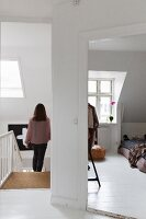 Woman walking down bright staircase and view into bedroom with sloping ceiling