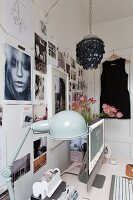 Desk with flatscreen monitor and retro table lamp below photo collage on wall