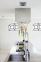 Island counter with sink and taps below stainless steel extractor hood; Art Nouveau windows in background