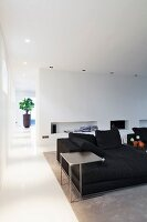 Delicate side table next to black sofa in front of niches in wall in modern interior