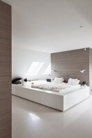 Bed on platform-style, custom bed installation against partition in attic bedroom