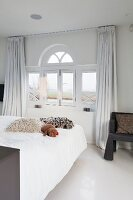 Fur scatter cushions on bed below window with semicircular fanlight in bedroom