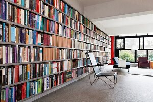 Metal-framed chair in front of bookcase in open-plan interior with Bauhaus ambiance