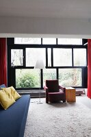 Blue couch and red armchair next to standard lamp in front of glass wall with frames reminiscent of Mondrian painting