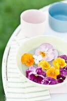 Pansies and violas floating in bowl on garden table