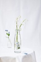 Lily of the valley in small pop bottle decorated with forget-me-not postage stamp