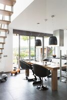 Upholstered swivel chairs at dining table below modern pendant lamps in open-plan kitchen with view of garden