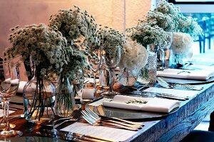Table elegantly set with opulent bouquets of white flowers