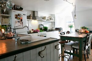 Counter with integrated sink on wooden base unit with hooks in front of dining area in simple kitchen