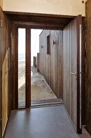 Camber Sands Beach Houses, Rye, United Kingdom. Architect: Walker and Martin, 2014; View out through front door directly onto sandy beach