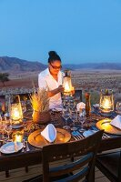 'Dune Camp' in Wolwedans, NamibRand Nature Reserve, Namibia, Africa – Sharon laying a table for a candlelight dinner