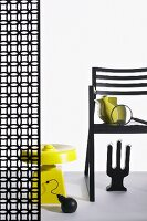 Chair and partition with graphic floral patter arrangement with bizarre objets d'art in black and yellow