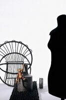 Ornamental structure of upturned wicker chair, wooden monkey on vase and profile of black tailors' dummy to one side