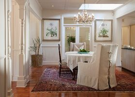Armchair with pale loose cover, chairs around table with tablecloth and chandelier in traditional, elegant dining room