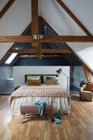 Double bed with bedspread against half-height partition screening ensuite bathroom in converted attic with exposed roof beams