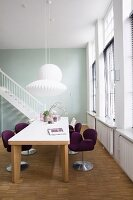 Purple, designer swivel chairs at solid wooden table below white pendant lamps; staircase in background
