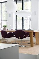 Purple swivel chairs at solid-wood dining table below white pendant lamps in front of lattice windows with louvre blinds