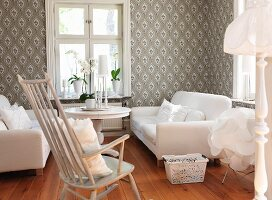 Comfortable living room with white sofa set, rocking chair, table below window and patterned wallpaper