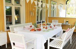 White wooden furniture around set table on veranda of yellow wooden house