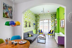 Colourful living area with neon-green wall and patterned wallpaper in retro interior