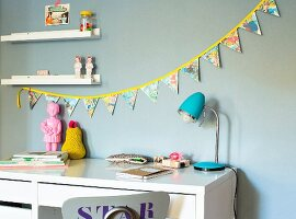 Hand-made, colourful bunting above desk in child's bedroom
