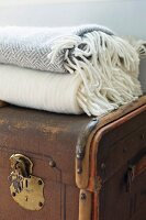 Old trunk with brass fittings and wool blankets on top