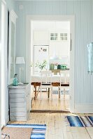 Wood-clad foyer in pastel blue with simple chest of drawers next to open doorway with view into rustic dining room