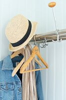 Straw hat and denim jacket on small, stainless steel coat rack on pale wooden wall