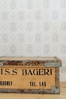 Old wooden crate with black stencilled lettering against wallpapered wall with pale grey retro pattern