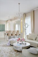 Round coffee table and white leather sofa on rug and dining area in background in luxurious interior