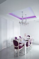 Elegantly set dining table and crystal chandelier in dining room with purple, indirect lighting on ceiling and Neo-Baroque, upholstered chairs