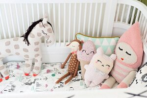 Fabric soft toys with closed, sleeping eyes in cot