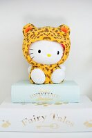 Hello Kitty figurine wearing leopard-print onesie sitting on books with gilt lettering on spines