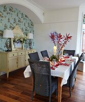 Table set for Christmas dinner, dark wicker chairs and pale sideboard in niche with floral wallpaper